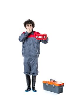흰색 벽에 판매 명판을 들고 제복을 입은 남성 노동자의 전면 보기