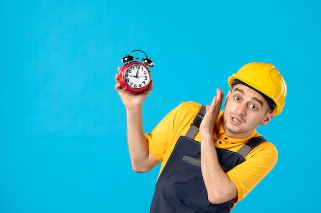 Вид спереди работника-мужчины в униформе, испуганного часов на синем