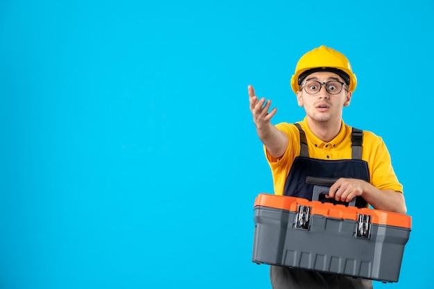 青のツールボックスを運ぶ黄色の制服を着た男性労働者の正面図