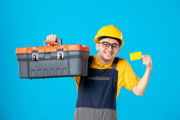 青のクレジットカードとツールボックスと黄色の制服を着た男性労働者の正面図