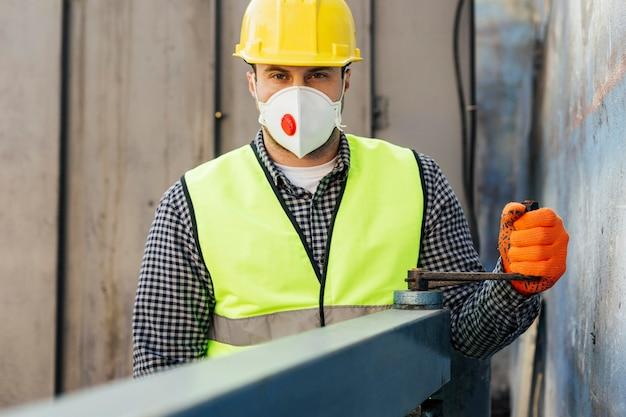 男性労働者の反射ベストと保護マスクの正面図