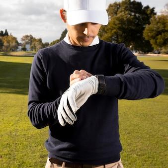 골프 필드에 그의 smartwatch를 조정하는 남자의 전면보기