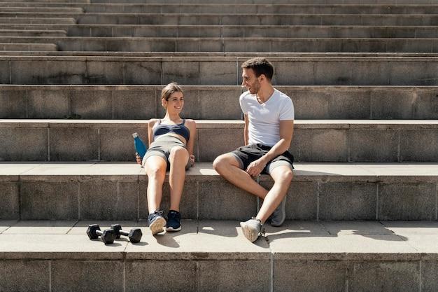운동하는 동안 단계에 휴식하는 남자와 여자의 전면보기