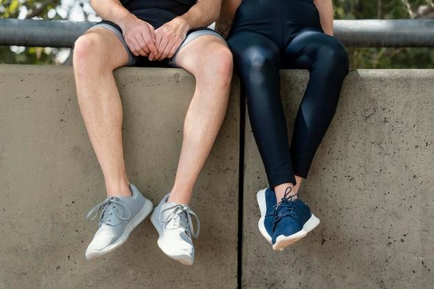 운동하는 동안 야외에서 함께 휴식하는 남자와 여자의 전면보기