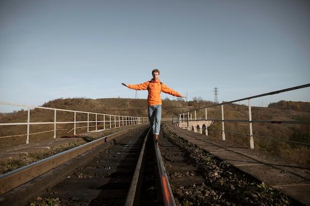 ロードトリップ中に鉄道でバランスをとる人の正面図