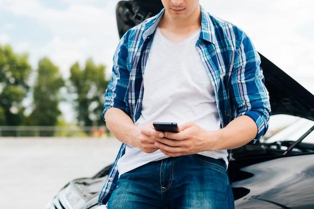 彼の携帯電話をチェックする男の正面図