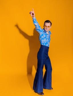 孤立した黄色の壁に70年代からのような服を着た男の正面図