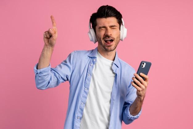 彼のヘッドフォンでスマートフォンから音楽を楽しんでいる男の正面図
