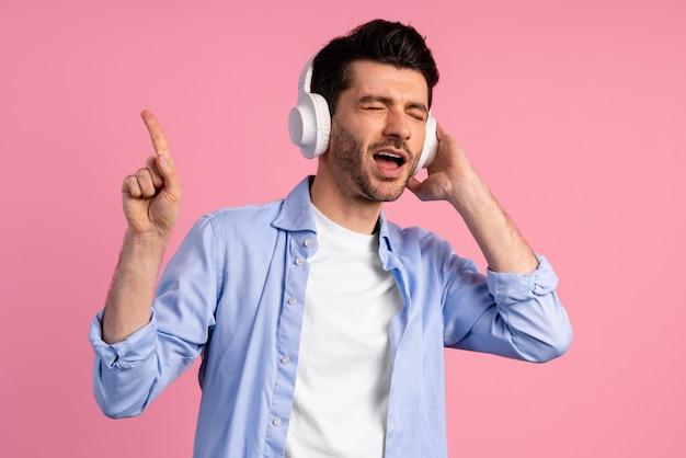 彼のヘッドフォンで音楽を楽しんでいる男の正面図