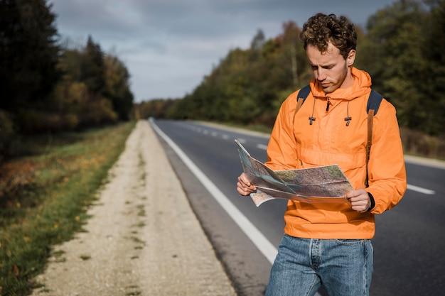 지도를 들고 도로를 따라 앉아있는 남자의 전면보기