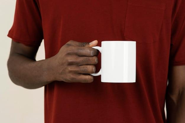 Вид спереди человека в футболке, держащего кружку