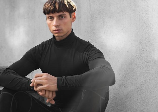 Вид спереди человека в спортивной одежде, позирующем на лестнице на открытом воздухе