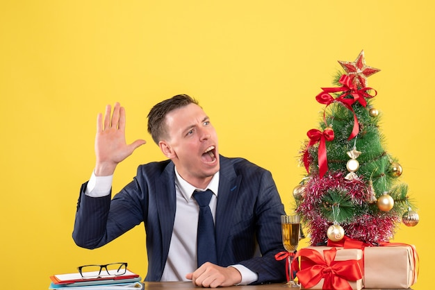 Вид спереди человека в костюме, приветствующего кого-то, сидящего за столом возле рождественской елки и подарков на желтом