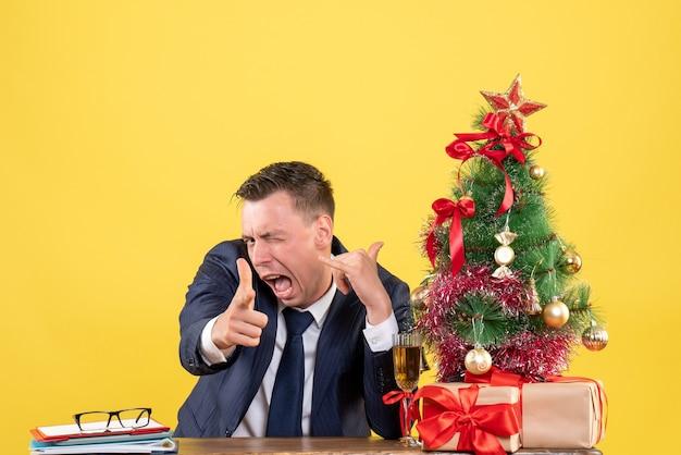 クリスマスツリーと黄色の贈り物の近くのテーブルに座ってカメラに指銃を保持しているスーツを着た男の正面図