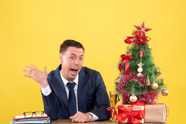 노란색에 크리스마스 트리와 선물 근처 테이블에 앉아 그의 입을 열고 정장에 남자의 전면보기
