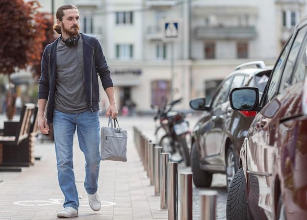 Вид спереди человека в городе с сумкой для ноутбука