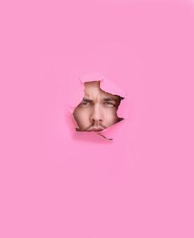 ピンクの背景の穴を通して見ている男の正面図