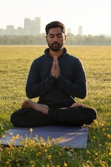 Вид спереди человека, медитирующего на открытом воздухе на коврике для йоги