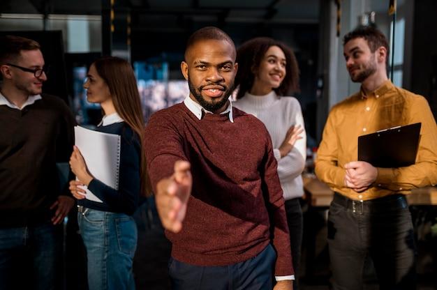 会議後の合意として握手を提供する男性の正面図