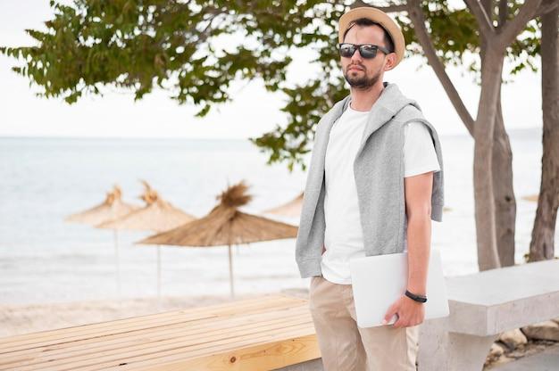 ラップトップを保持しているビーチで男の正面図