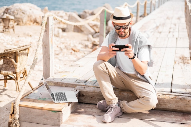 ノートパソコンとスマートフォンに取り組んでいるビーチの桟橋の男の正面図