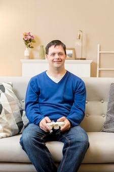 自宅のソファーでビデオゲームをプレイしている男の正面図
