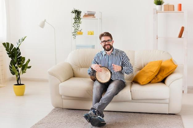 Вид спереди человека на диване с барабаном