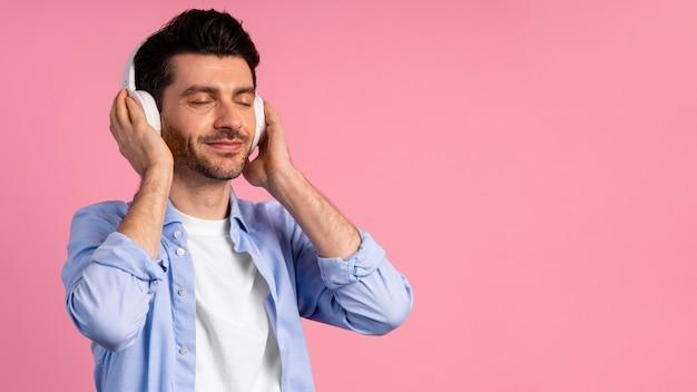 彼のヘッドフォンで音楽を演奏する男の正面図