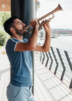 Вид спереди человека, играющего на трубе