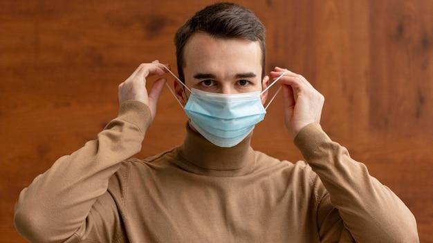 Вид спереди человека, надевающего медицинскую маску