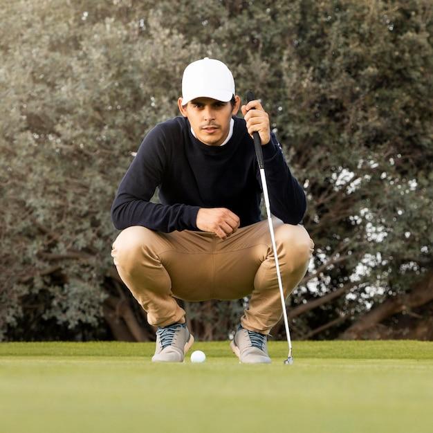 フィールドでゴルフボールの上にしゃがむ男の正面図