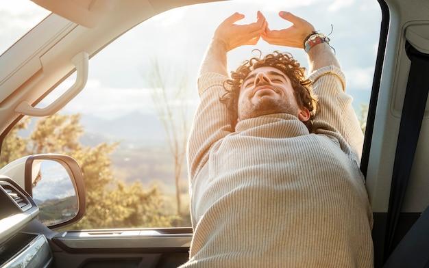 도로 여행을하는 동안 차에서 스트레칭하는 남자의 전면보기
