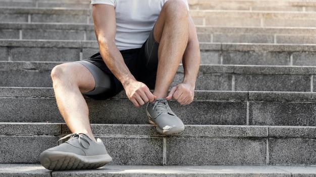 운동하기 전에 그녀의 구두 끈을 묶는 남자의 전면보기