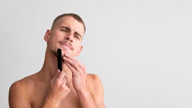 コピースペースで彼のひげに櫛を使用して男の正面図
