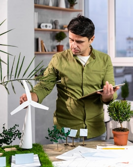 Вид спереди человека, использующего планшет рядом с экологически чистым макетом проекта ветроэнергетики