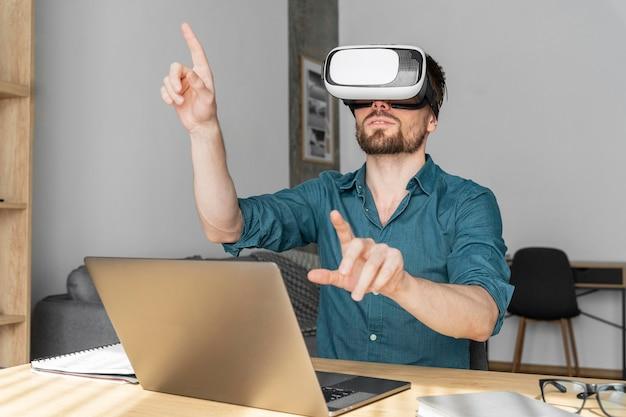 Вид спереди человека, использующего гарнитуру виртуальной реальности дома с ноутбуком