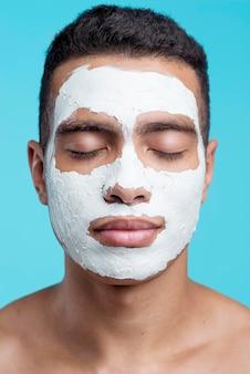 上の美容フェイスマスクを持つ男の正面図