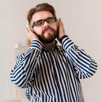 音楽を楽しむヘッドフォンを持つ男の正面図