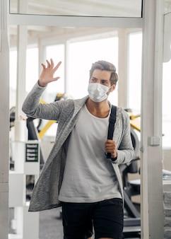 ジムで手を振っている医療マスクを持つ男の正面図