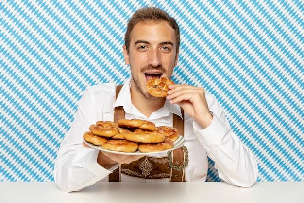 柔らかいプレッツェルプレートを持つ男の正面図