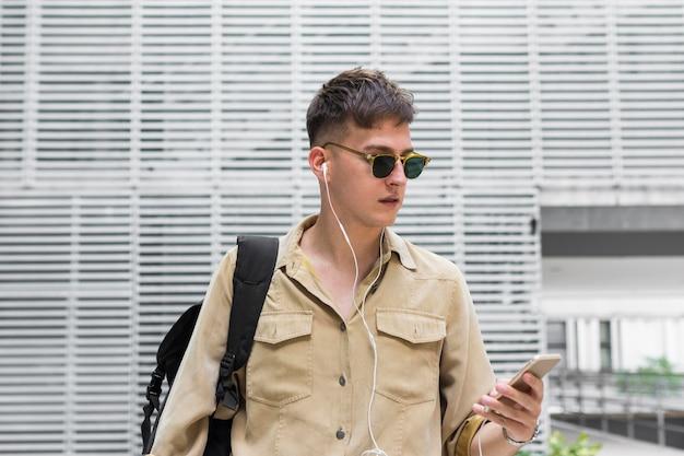 イヤホンで音楽を聴くサングラスを持つ男の正面図