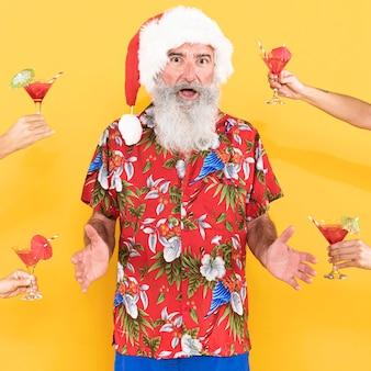 トロピカルシャツとクリスマス帽子を持つ男の正面図