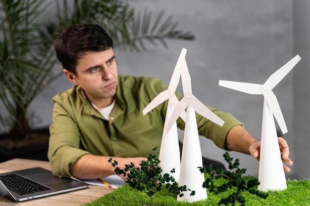 Вид спереди человека, работающего над экологически чистым ветроэнергетическим проектом с ноутбуком и ветряными турбинами