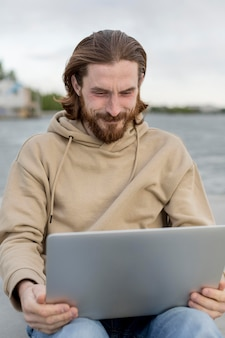 Вид спереди человека, работающего на ноутбуке рядом с озером