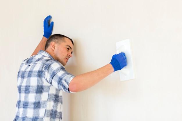Вид спереди человека, работающего на стене