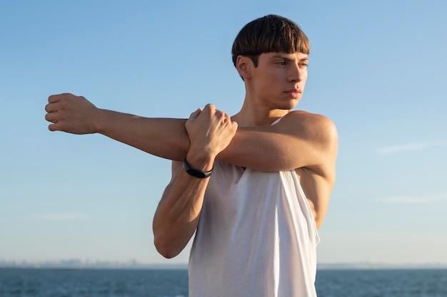 ビーチで運動している男の正面図