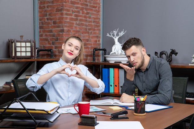 オフィスでカメラのポーズをとってテーブルに座っている管理チームの正面図