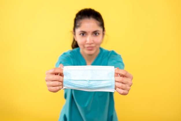 노란색 격리 된 벽에 여성 손에 의료 마스크의 전면보기