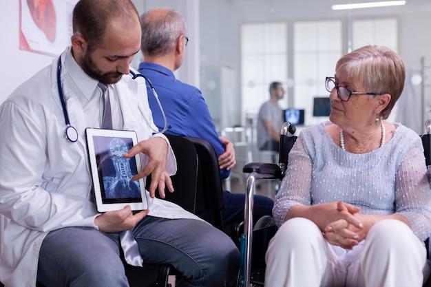 태블릿을 사용하여 방사선 촬영을 보여주는 revovery 치료에 대해 장애인 노인 여성과 논의하는 의료 의사의 전면보기