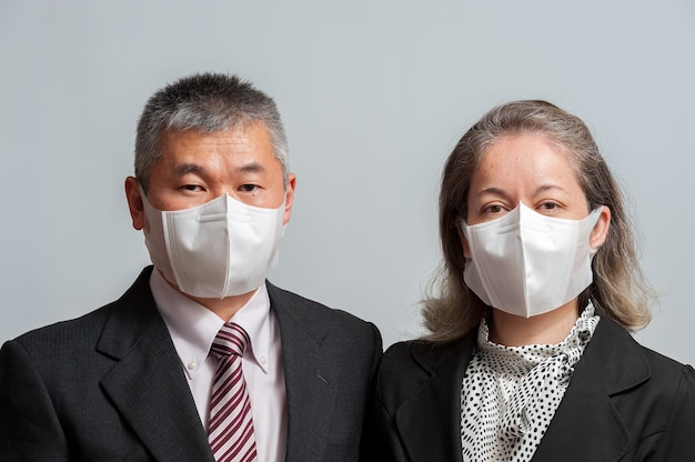 白いサージカルマスクを身に着けているフォーマルな服装で中年のアジアのカップルの正面図